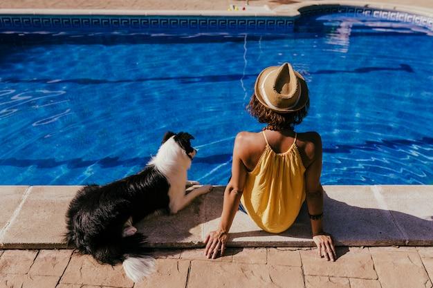 Jonge vrouw en haar border collie-hond bij het zwembad Premium Foto
