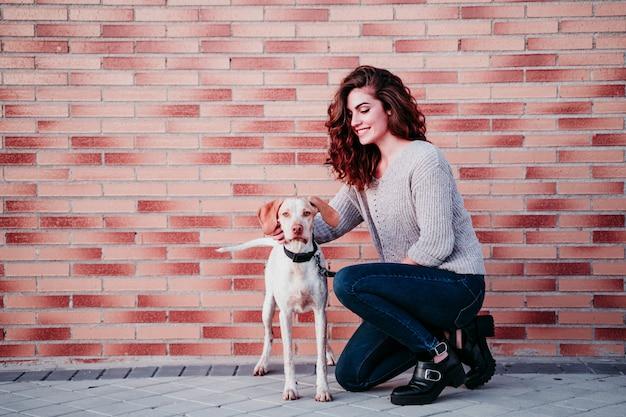 Jonge vrouw en haar hond in de stad. staande bij een bakstenen muur Premium Foto