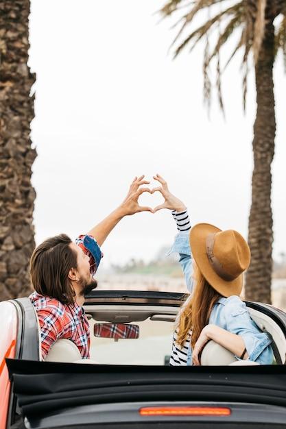 Jonge vrouw en man die symbool van hart tonen en uit auto leunen Gratis Foto
