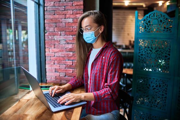 Jonge vrouw freelancer die een gezichtsmasker van de geneeskunde draagt dat op afstand werkt op een computer in een café tijdens een pandemie. sociale afstand en bescherming van de gezondheid tegen virussen op openbare plaatsen Premium Foto
