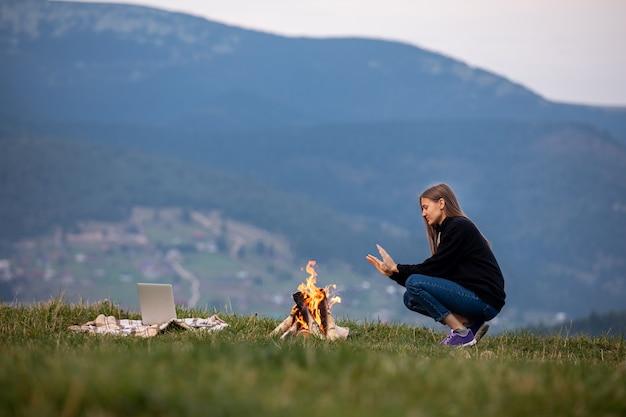 Jonge vrouw freelancer zit bij het vuur en verwarmt zijn handen in de bergen in de avond. toeristische meisje rusten en die op laptop buiten werken Premium Foto