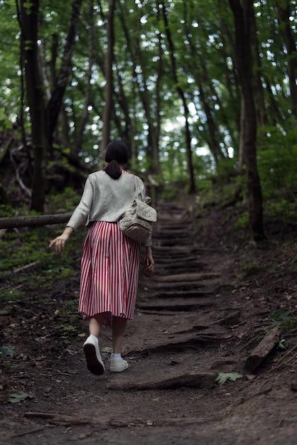 Jonge vrouw gaat op een bospad. het meisje loopt zelf door het bos. wild park. achteraanzicht Premium Foto