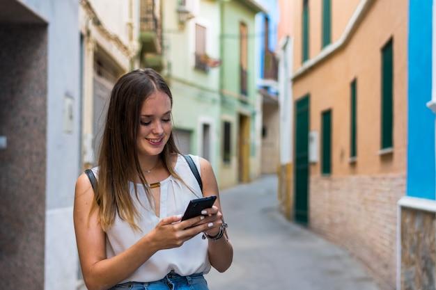 Jonge vrouw gebruikt haar smartphone in de straat Premium Foto