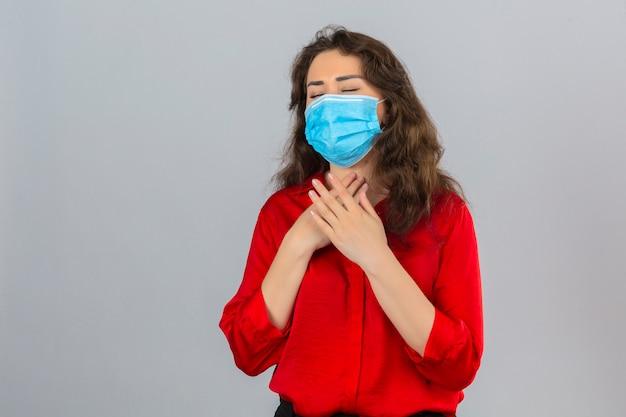 Jonge vrouw, gekleed in een rode blouse in medisch beschermend masker kijkt onwel haar nek aanraken en lijdt aan keelpijn over geïsoleerde witte achtergrond Gratis Foto