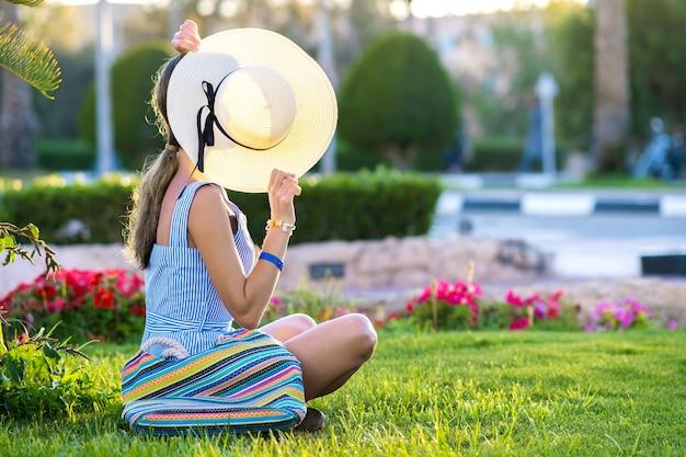 Jonge vrouw, gekleed in lichtblauwe zomerjurk en gele strooien hoed ontspannen op groen gras Premium Foto