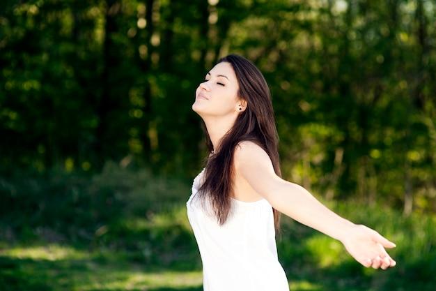 Jonge vrouw genieten van de zomer in een park Gratis Foto