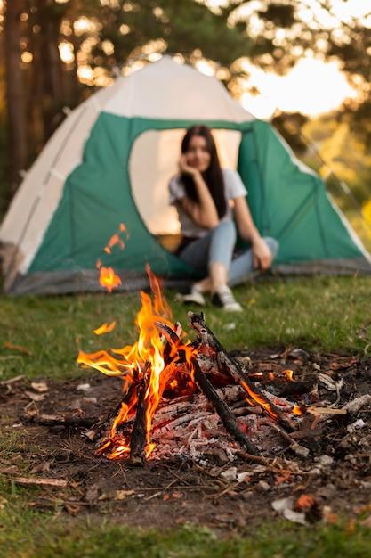 Jonge vrouw genieten van vreugdevuur in de natuur Gratis Foto
