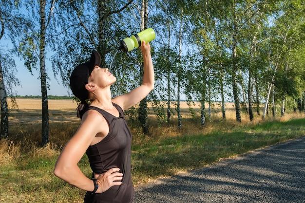 Jonge vrouw gieten water uit de fles op haar gezicht rusten na een zware training Premium Foto
