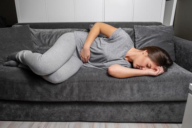 Jonge vrouw heeft buikpijn op de bank liggen Premium Foto