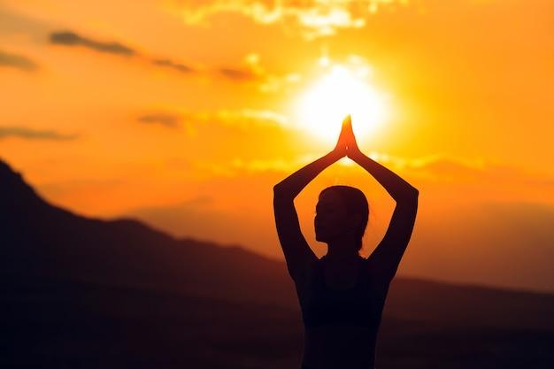 Jonge vrouw het beoefenen van yoga bij zonsondergang op prachtige berglocatie. Premium Foto