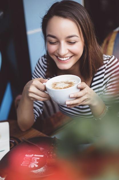 Jonge vrouw het drinken koffie in stedelijke koffie Gratis Foto