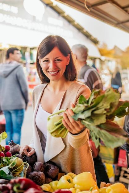 Jonge vrouw het kopen van groenten op de groene markt. Premium Foto