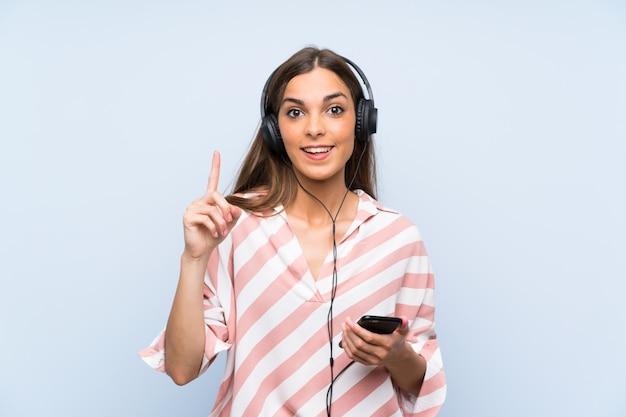 Jonge vrouw het luisteren muziek met mobiel die een groot idee benadrukken Premium Foto