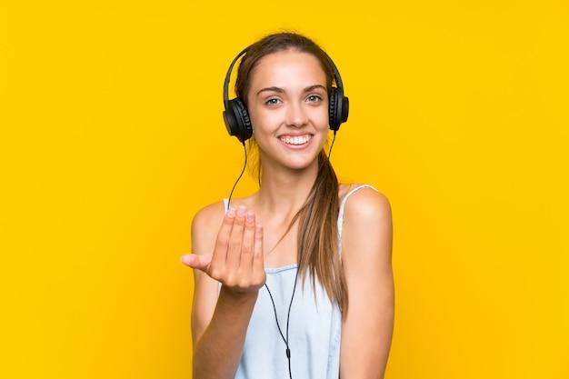 Jonge vrouw het luisteren muziek over geïsoleerde gele muur die met hand uitnodigt te komen. blij dat je bent gekomen Premium Foto