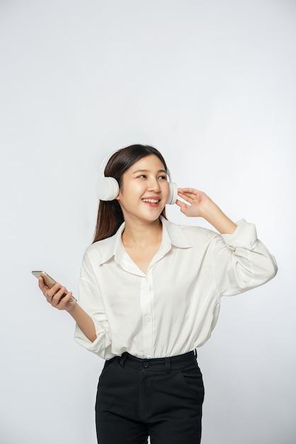 Jonge vrouw hoofdtelefoon dragen en luisteren naar muziek op een smartphone Gratis Foto
