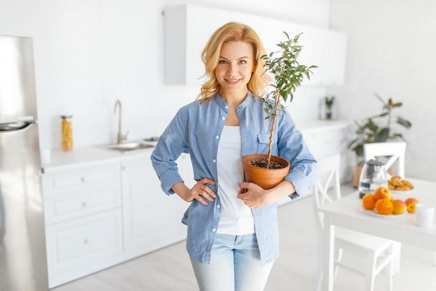 Jonge vrouw houdt een bloem in een pot op de keuken met sneeuwwit interieur. Premium Foto