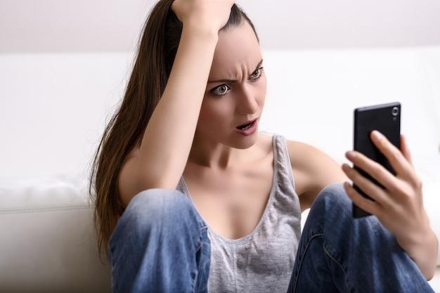 Jonge vrouw houdt zijn hoofd en kijkt naar de smartphone. verontrust door wat hij zag Premium Foto