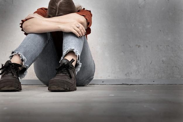 Jonge vrouw huilt en zit in de buurt van een lege muur, eenzaam verdrietig en depressief meisje houdt haar hoofd ingedrukt Premium Foto
