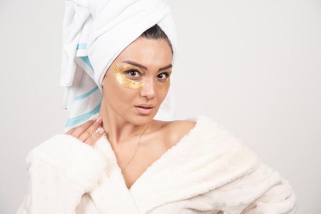 Jonge vrouw in badjas en cosmetische ooglapjes poseren Gratis Foto