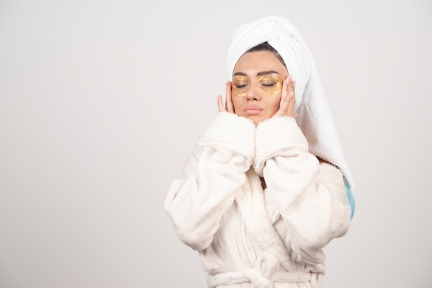 Jonge vrouw in badjas en cosmetische ooglapjes wat betreft haar gezicht Gratis Foto