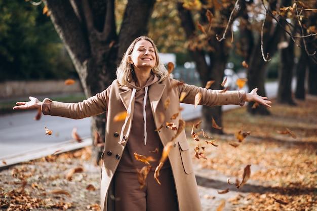 Jonge vrouw in beige pak buiten in een herfst park Gratis Foto