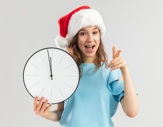 Jonge vrouw in blauwe bovenkant en de klok die van de de holdingsmuur van de santahoed met gelukkig en positieve wijsvinger richten Gratis Foto