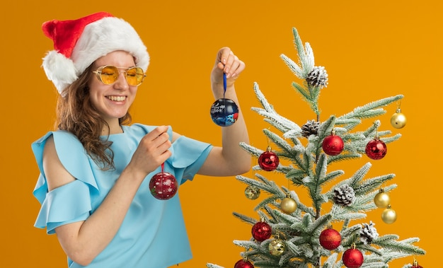 Jonge vrouw in blauwe top en kerstmuts met gele bril met kerstballen blij en vrolijk met een grote glimlach op het gezicht staande naast een kerstboom over oranje achtergrond Gratis Foto