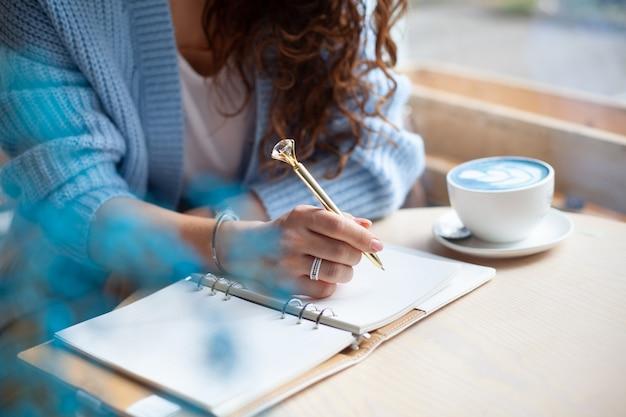 Jonge vrouw in blauwe warme trui zit in de buurt van het grote raam van de coffeeshop en het schrijven van een boodschappenlijstje voor kerstmis met een kopje blauwe latte. kerstvakantie plannen. concept organiseren en plannen. Premium Foto
