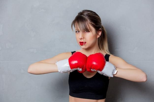 Jonge vrouw in bokshandschoenen op grijze achtergrond. zaklampstijl uit de jaren 90 Premium Foto