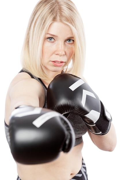 Jonge vrouw in bokshandschoenen. slagvaardigheid en moed. geã¯soleerd op witte achtergrond Premium Foto