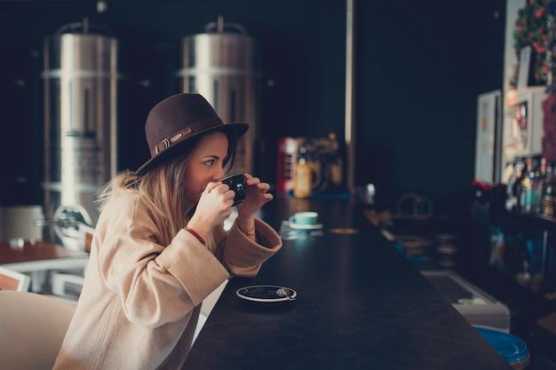 Jonge vrouw in bruine sweater en bruine hoed het drinken koffie in een koffiewinkel Premium Foto