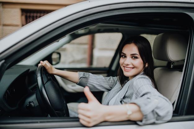 Jonge vrouw in de auto zitten en duimen opdagen Gratis Foto