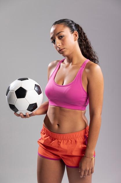 Jonge vrouw in de bal van de sportkledingsholding Gratis Foto