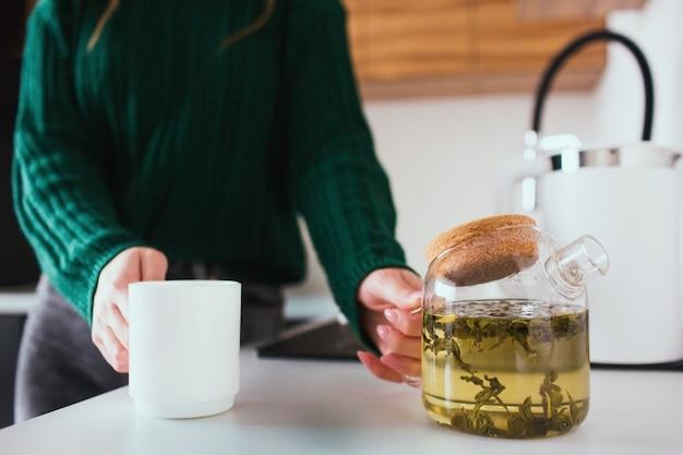 Jonge vrouw in de keuken tijdens de quarantaine. de theepot van de meisjesgreep en witte kop in handen. gaat wat thee schenken voor lunch of diner. Premium Foto