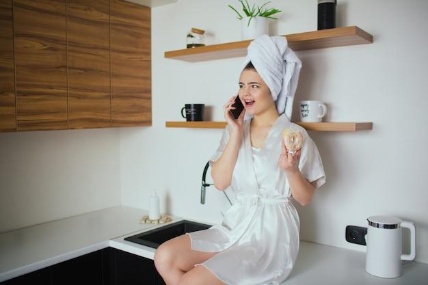 Jonge vrouw in de keuken tijdens de quarantaine. meisje na douche zitten en praten over de telefoon. houd smakelijke donut in de hand. online gesprek. Premium Foto