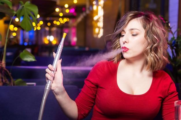 Jonge vrouw in de rode jurk rookt een waterpijp aan de waterpijp bar. Premium Foto