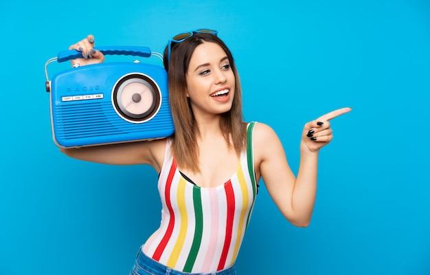 Jonge vrouw in de zomervakantie die over blauw een radio houdt Premium Foto