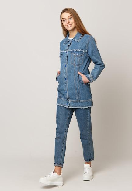 Jonge vrouw in denimkostuum op een witte achtergrond Premium Foto