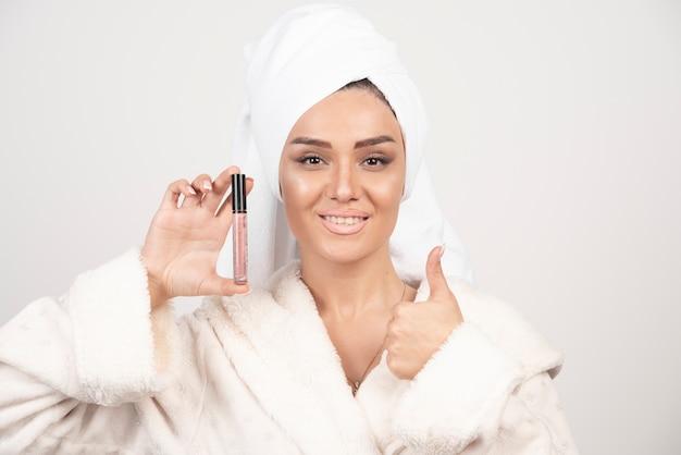 Jonge vrouw in een badjas die een lippenstift houdt en een duim toont Gratis Foto
