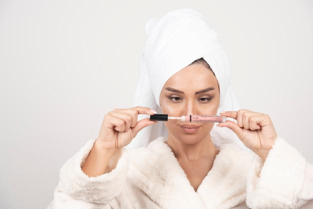 Jonge vrouw in een badjas die een lippenstift opent. Gratis Foto