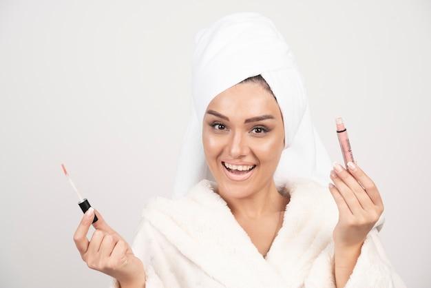 Jonge vrouw in een badjas met een lippenstift. Gratis Foto