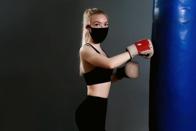 Jonge vrouw in een beschermend masker raakt een bokszak. beschermende maskers tegen virusinfectie. trainen tijdens quarantaine in de sportschool Premium Foto