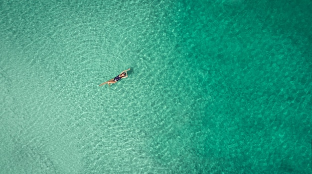 Jonge vrouw in een bikini die op de rug op het witte zand dichtbij de golven van blauwe overzees ligt Premium Foto