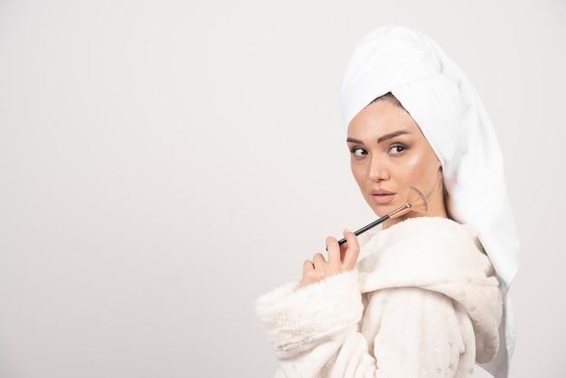 Jonge vrouw in een de samenstellingsborstel van de badjasholding Gratis Foto