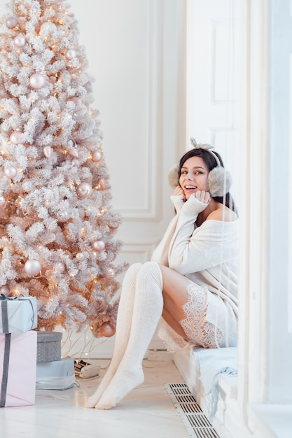 Jonge vrouw in een elegante jurk in de buurt van de kerstboom Gratis Foto