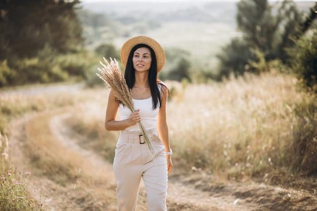 Jonge vrouw in een hoed op een gebied van tarwe Gratis Foto