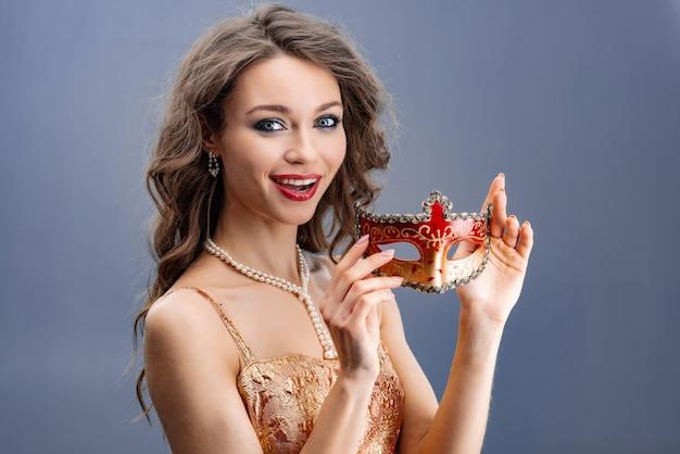 Jonge vrouw in een parelketting verraste het bekijken de camera en het tonen van een carnaval-masker Premium Foto