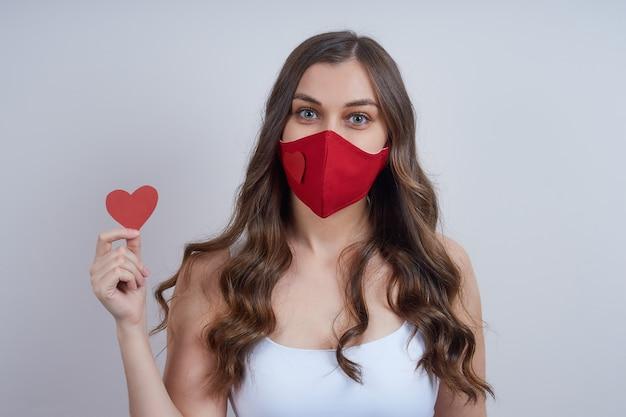 Jonge vrouw in een rood beschermend masker, met een hart van papier in haar hand Premium Foto