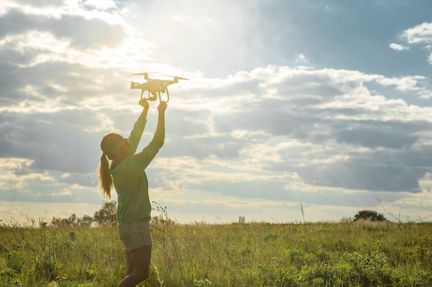 Jonge vrouw in een veld lanceert de drone in de lucht Gratis Foto