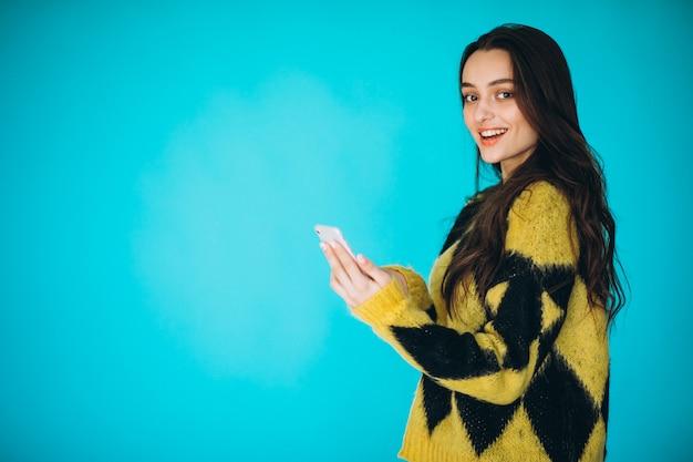Jonge vrouw in een warme trui met behulp van de telefoon Gratis Foto